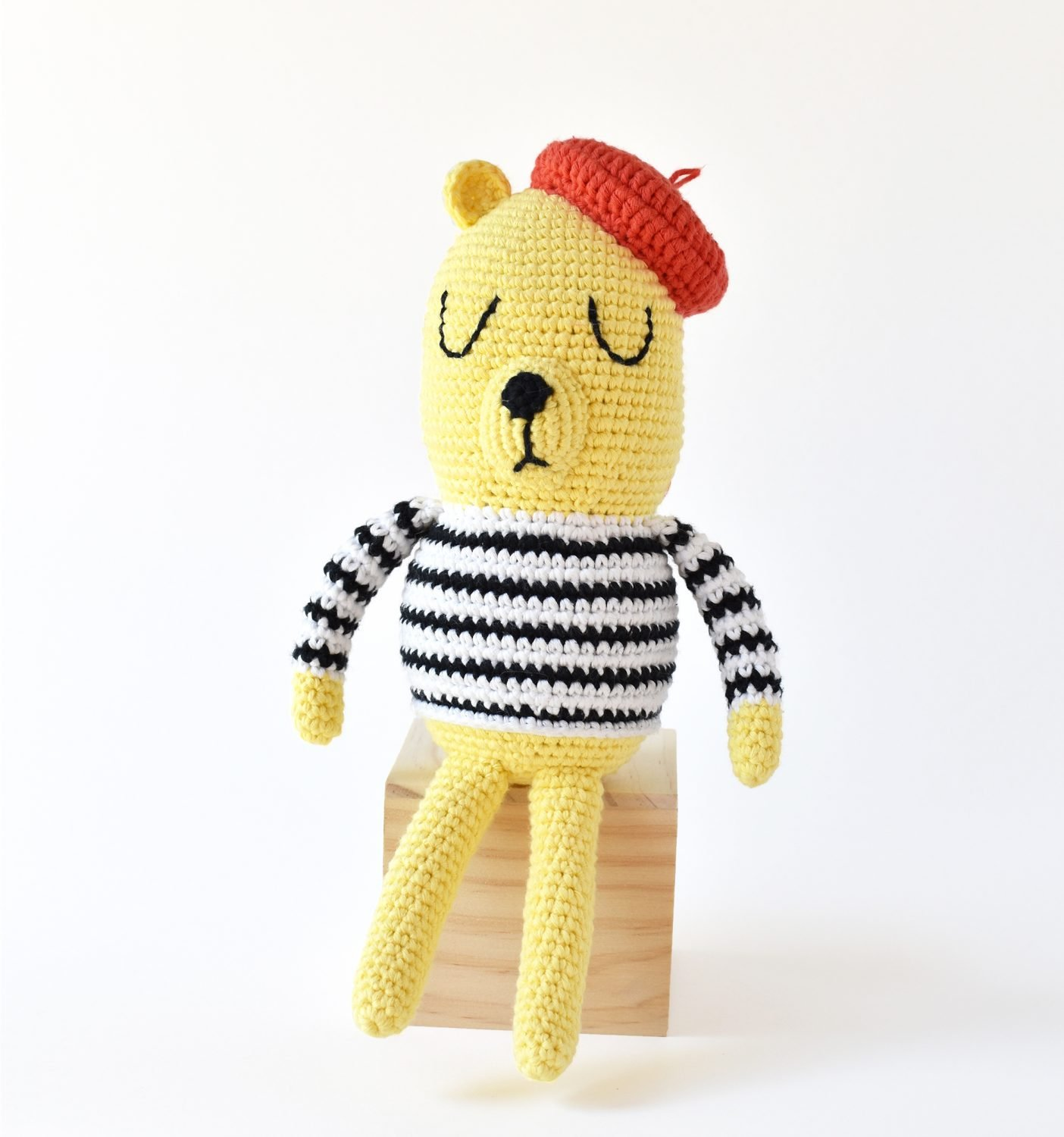 Showing Monsieur Bear amigurumi doll with his striped crochet sweater and crochet beret. This free crochet pattern was made by Tiny Curl.