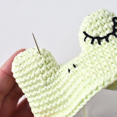 Amigurumi face embroidery with both nostrils complete and the second eye beginning.