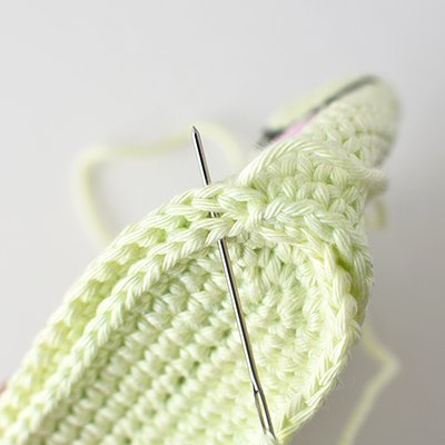Using bottom panel yarn tail to show how to thread tapestry needle and sew bottom panel to body.