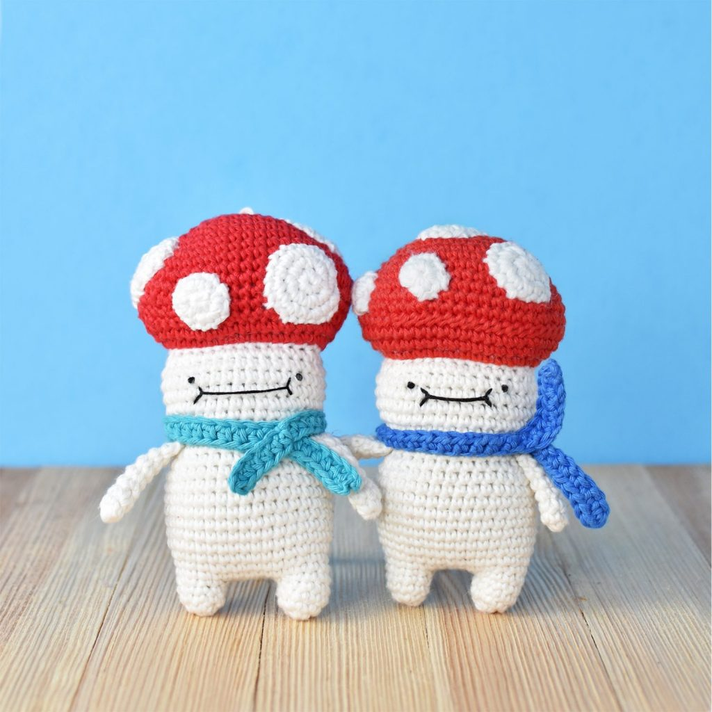 Free amigurumi Christmas ornament pattern, an amigurumi crochet pattern by Tiny Curl. Two amigurumi Christmas ornament Mushies standing next to each other. Both made with this free amigurumi Christmas ornament pattern.